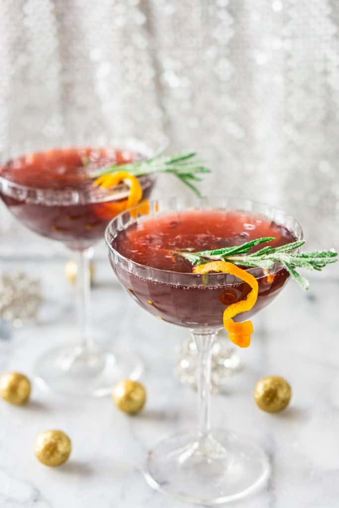 Looking at two sparkling martinis with glitter balls around it against a shimmery background.
