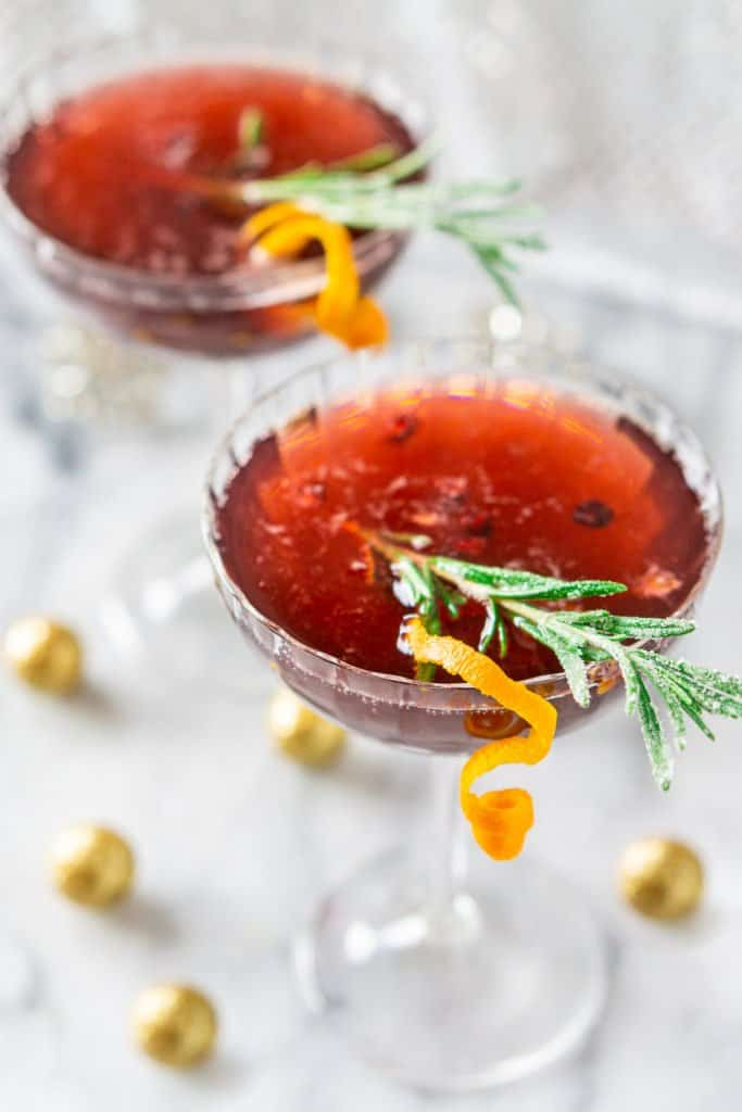 Looking down on a sparkling pomegranate martini with candied rosemary and an orange twist on the side.