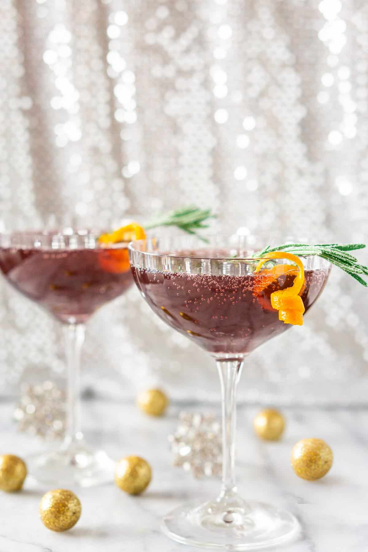 A sparkling pomegranate martini on a marble board with glittery balls around it.
