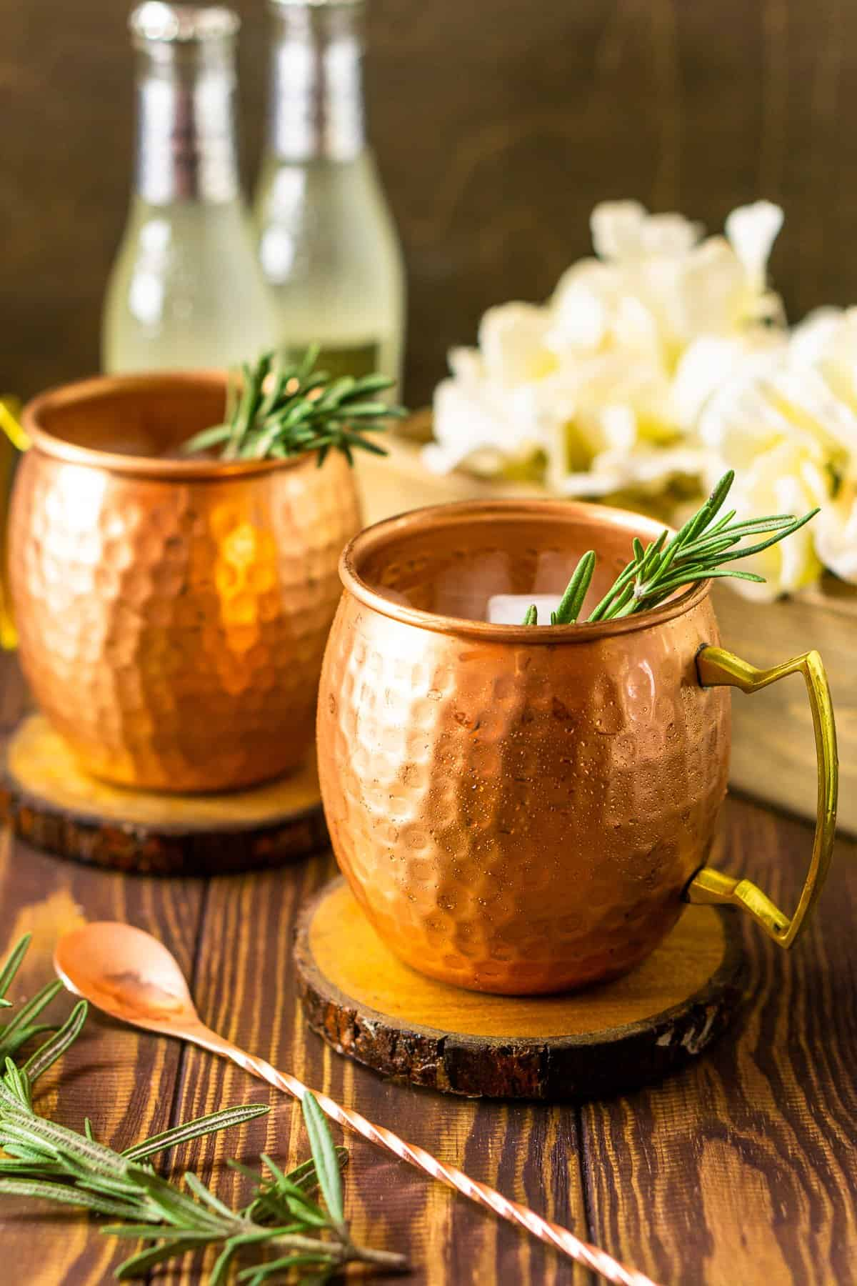 Two rosemary Kentucky mule with ginger beers in the background on a wooden board.