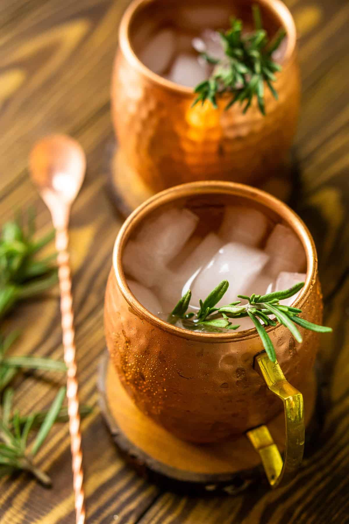 An aerial view of two rosemary mules with a bar spoon on a wooden board to the side.