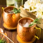 Two rosemary Kentucky mules with a copper bar spoon to the left and a box of white flowers in the background.