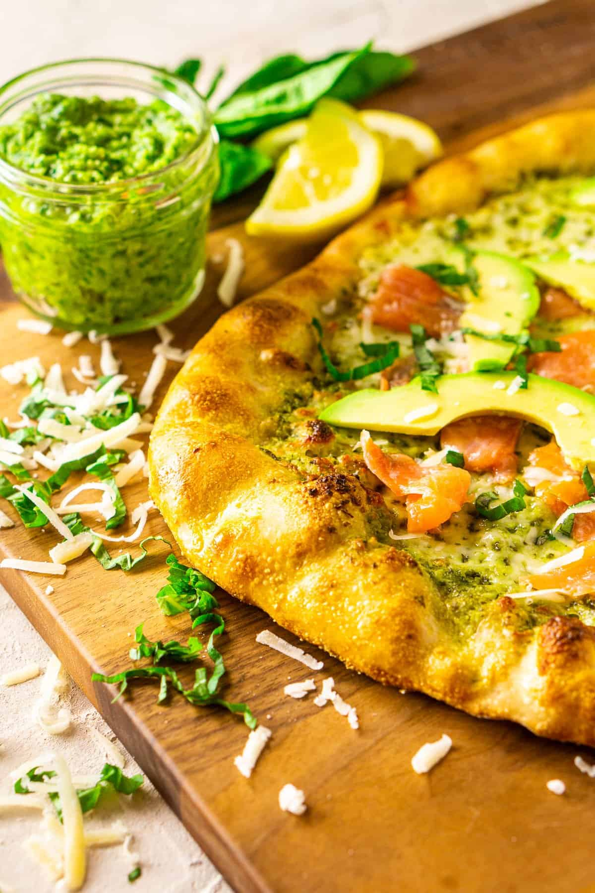 The smoked salmon and avocado pizza with pesto on a wooden cutting board with a jar of pesto, herbs and cheese around it.
