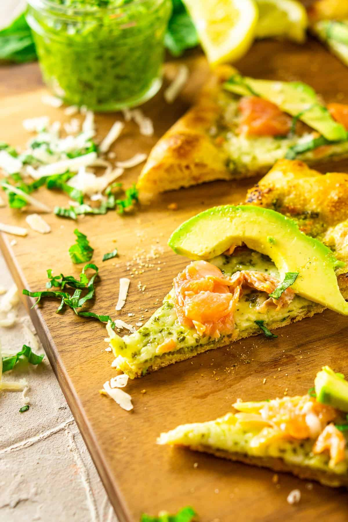 A slice of the smoked salmon and avocado pizza on the wooden cutting board with other slices around it.