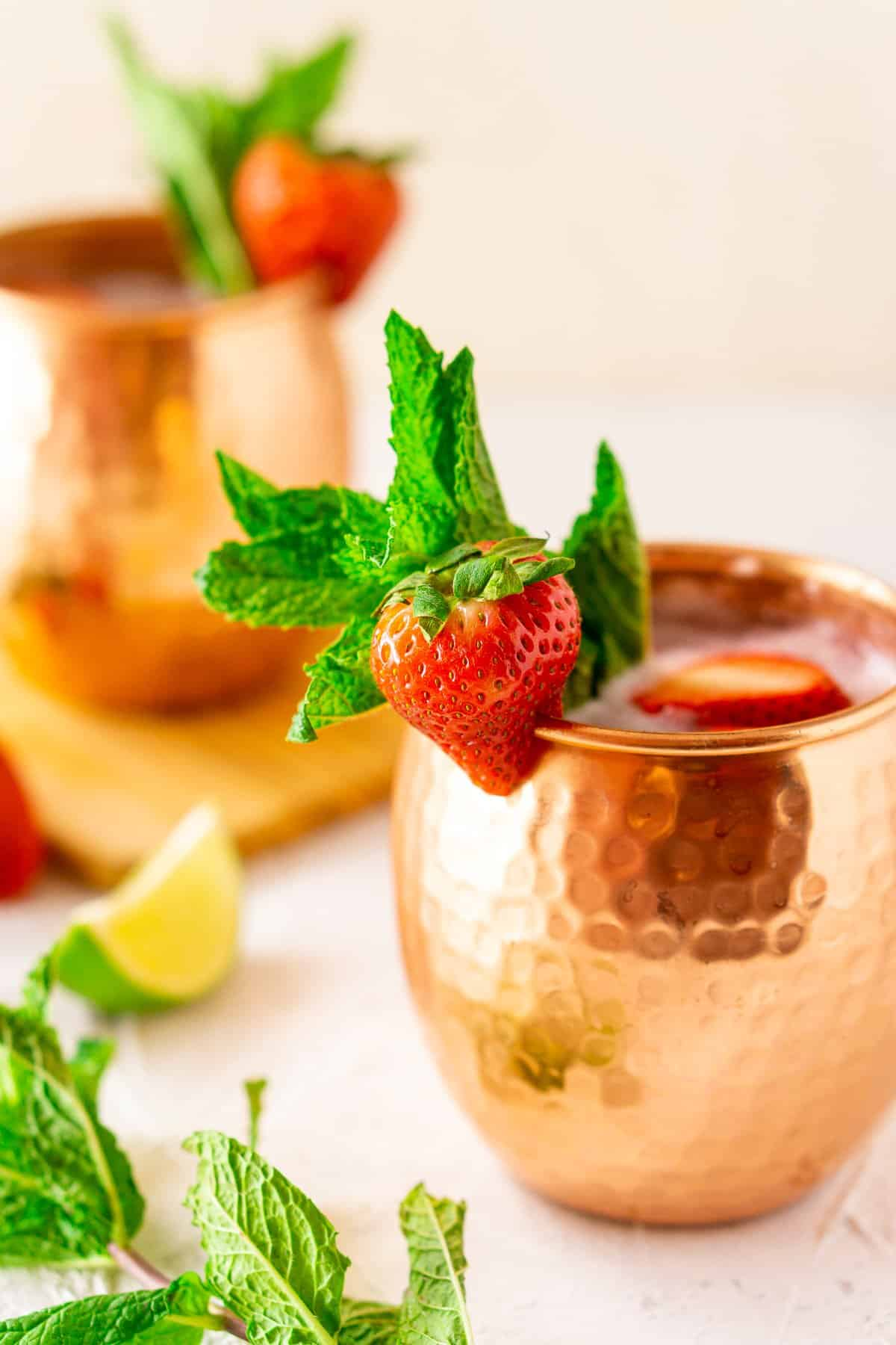 Two strawberry mint Moscow mules with a lime slice and mint sprig next to them on a white board.