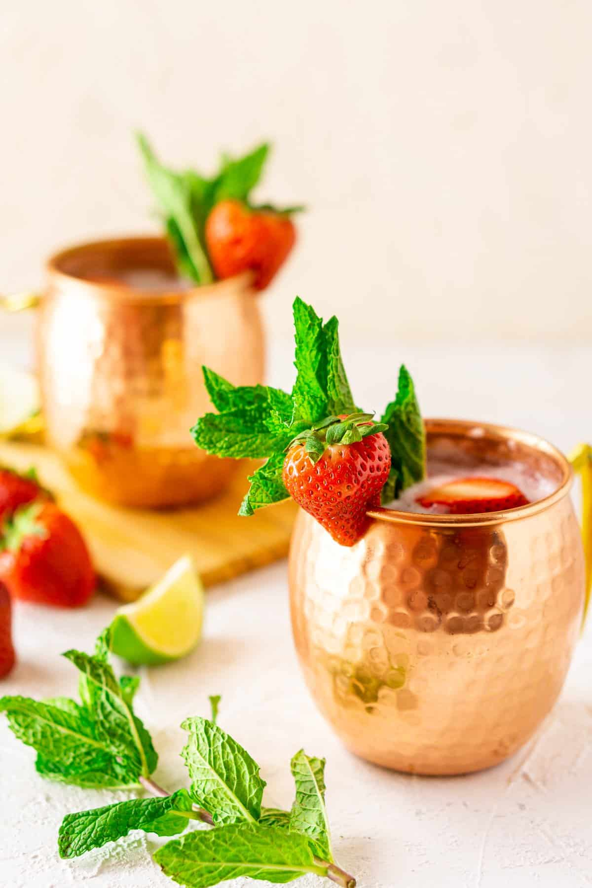 Two strawberry Moscow mules in copper mugs with fresh mint, lime slices and strawberries on the side.