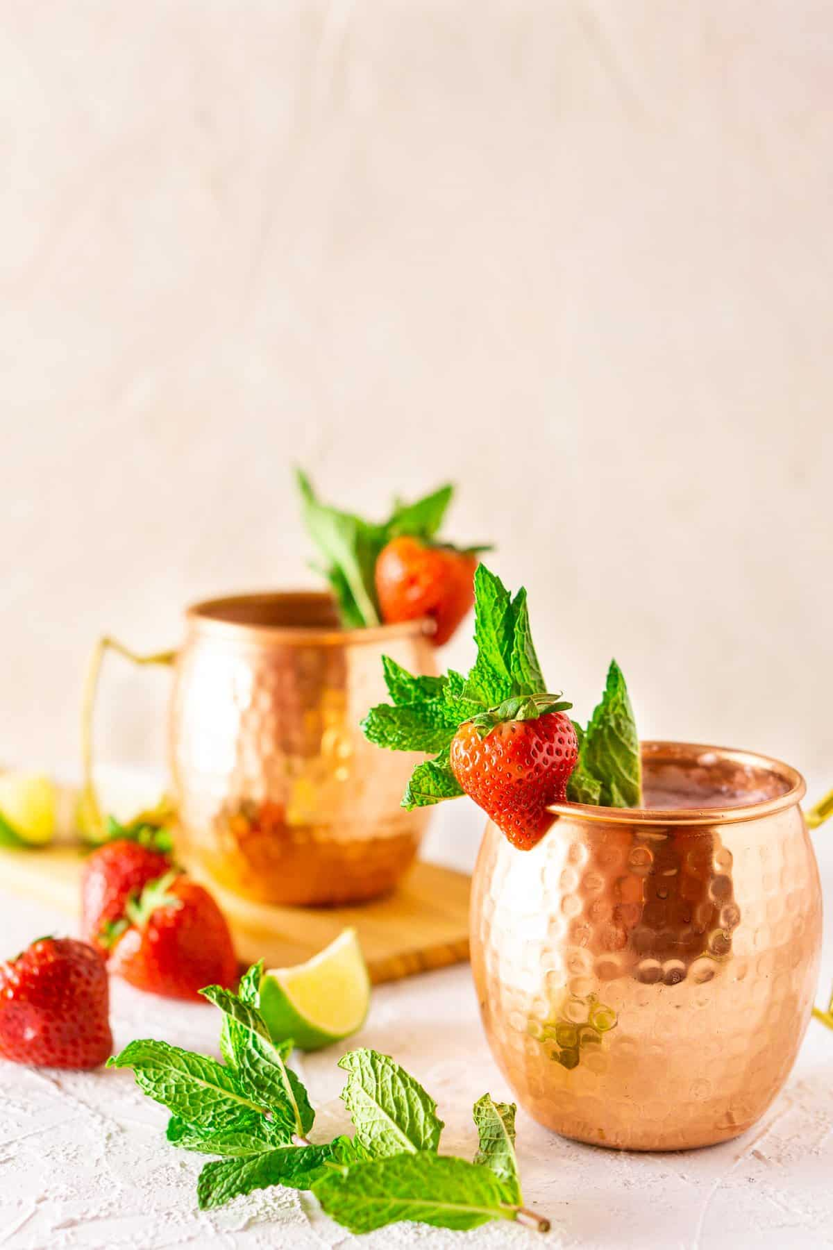 The strawberry Moscow mules on a white board with a mint sprig to the left.
