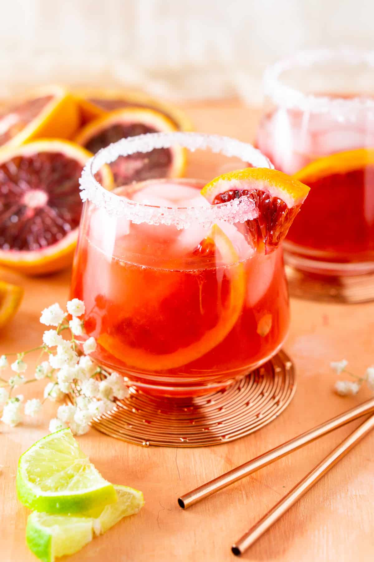 Two blood orange margaritas with cut-up blood oranges and lime slices.
