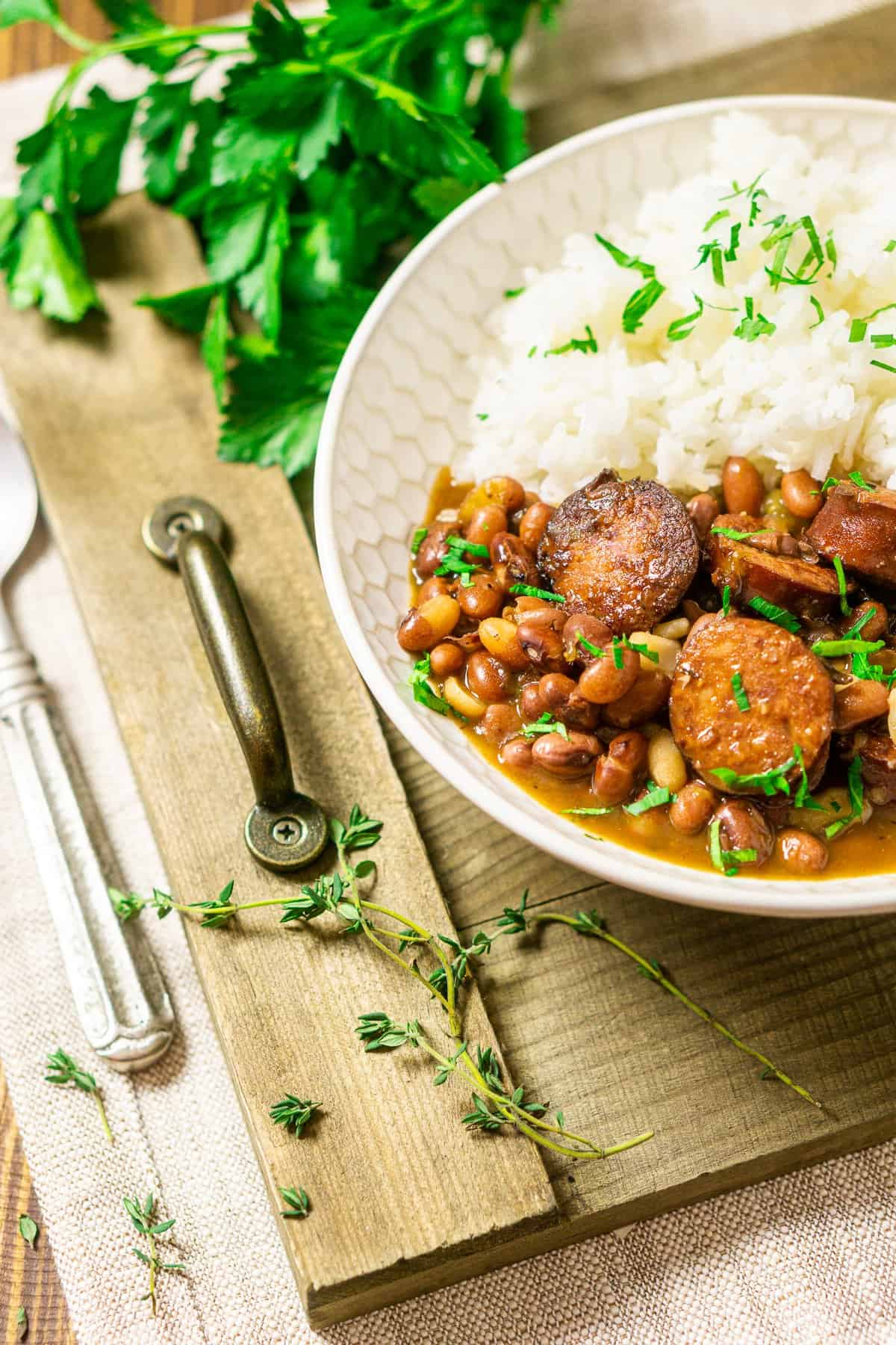 Looking down at a bowl of Instant Pot red beans and rice on a wooden tray with thyme and parsley around it.