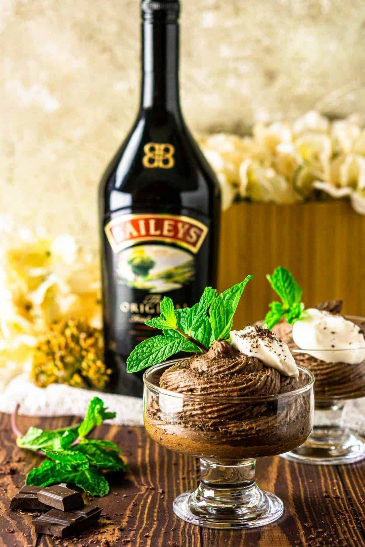 The Baileys mousse with a bottle of Irish cream and white flowers behind it on a wooden board.