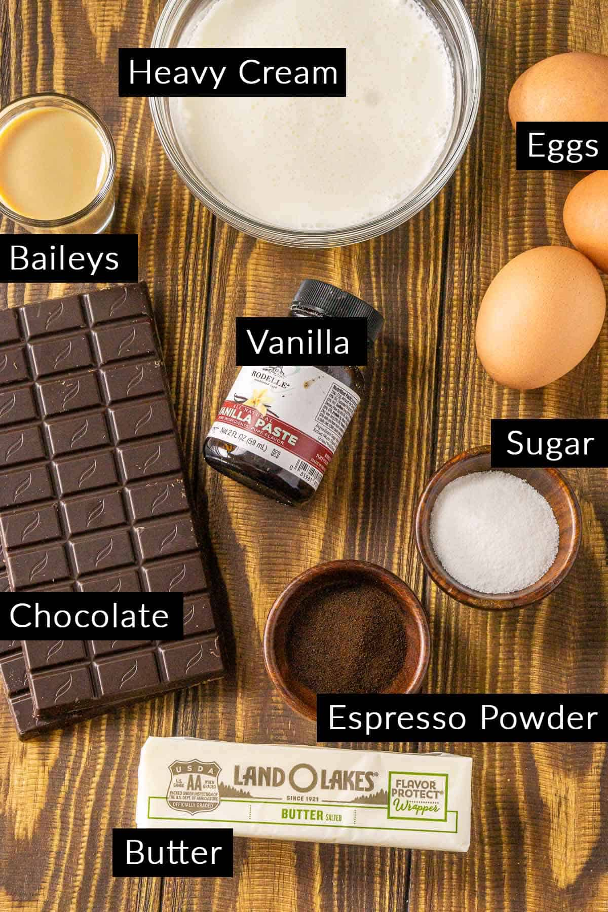 The Baileys mousse ingredients with black and white labels on a wooden background.