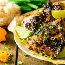 A plate of grilled Jamaican jerk chicken with peppers, rice and green onion.