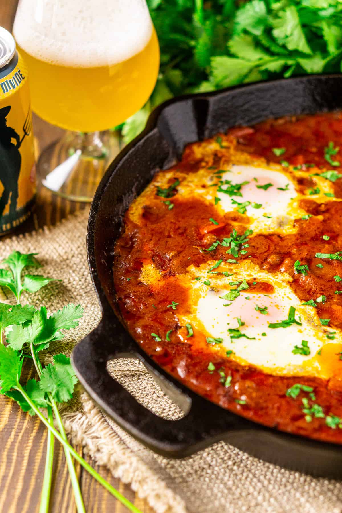 The Lamb Shakshuka with tomato-beer sauce on a wooden board with a saison behind it.