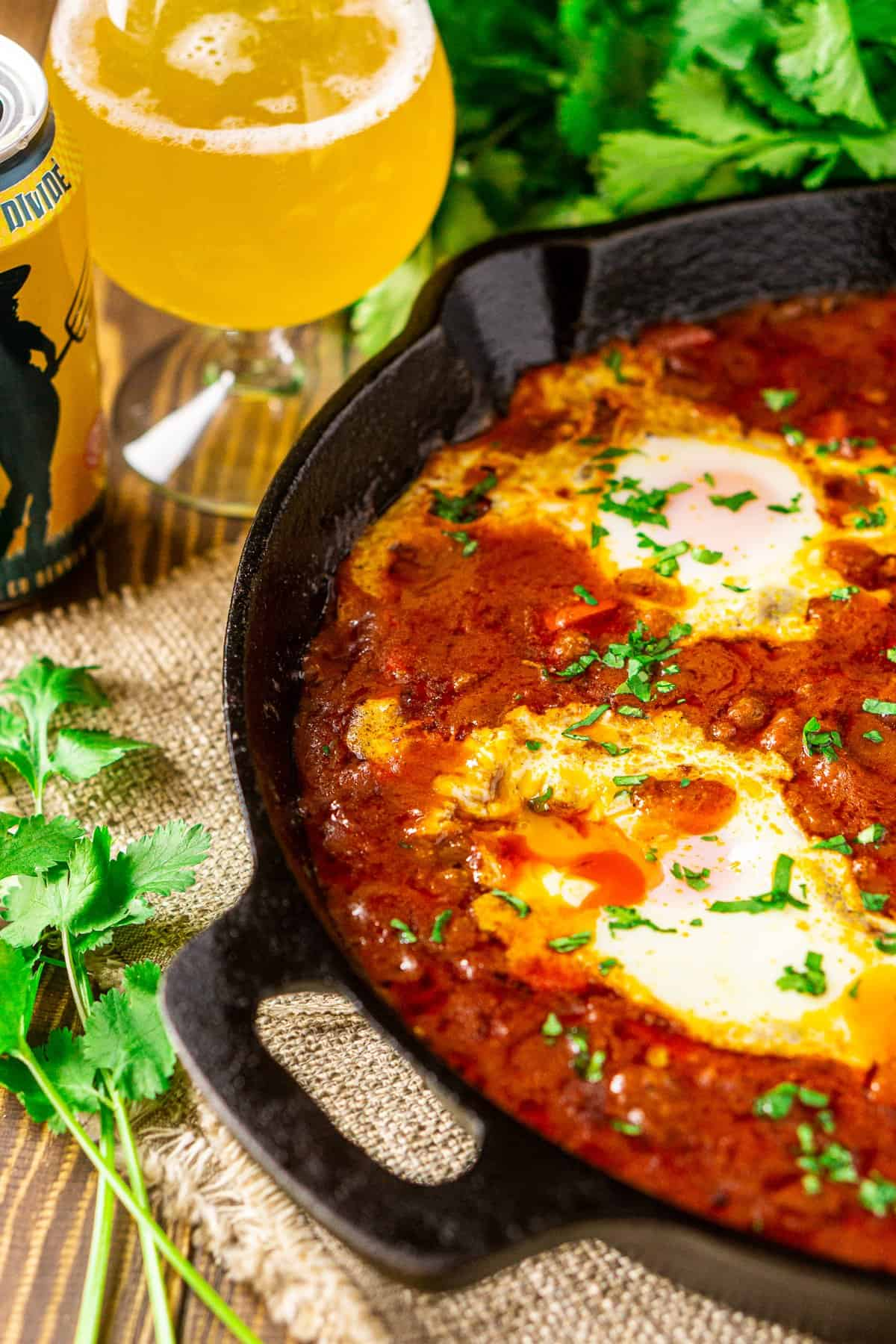 The beer and Lamb Shakshuka after breaking into the yolks with cilantro behind it.