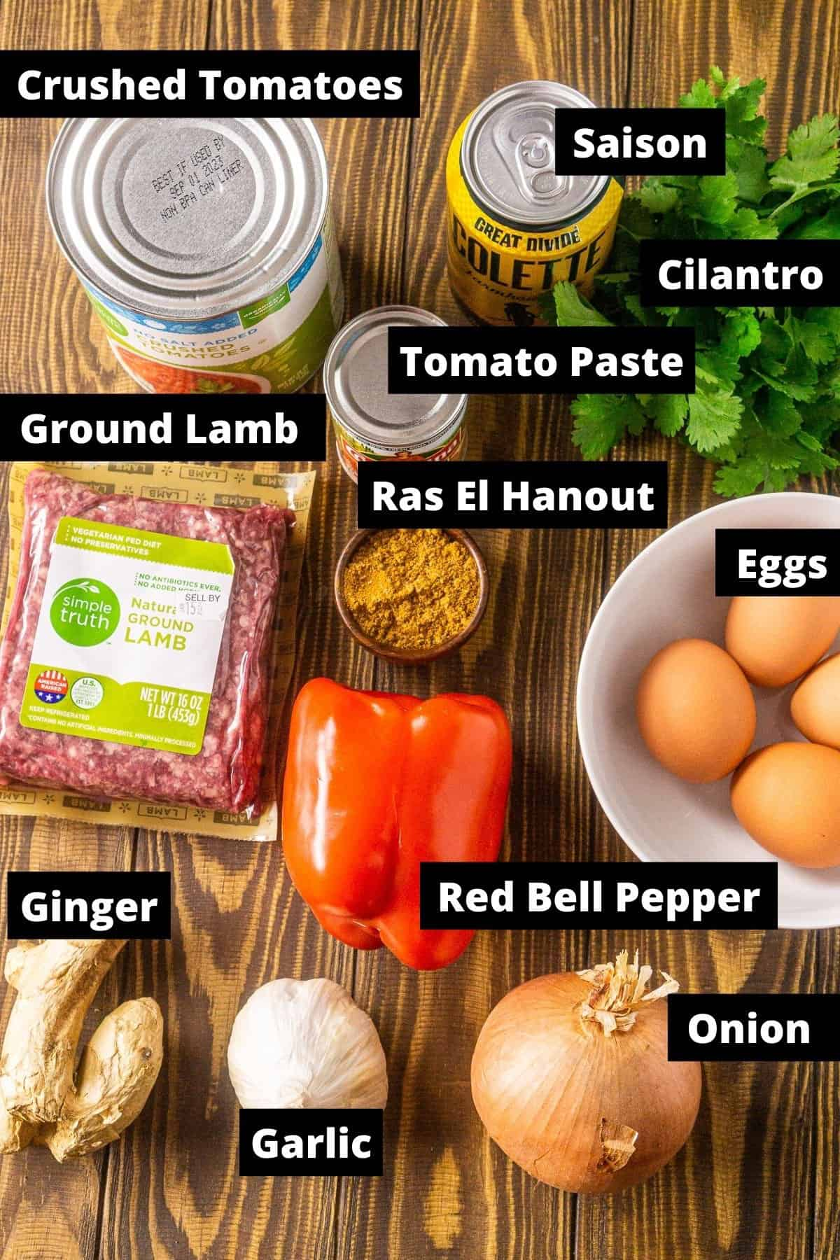 The Lamb Shakshuka ingredients with black and white labels on a wooden board.