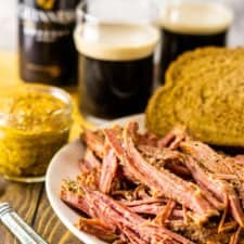 A plate of shredded slow cooker Guinness corned beef with mustard on the side and two beers in the background.