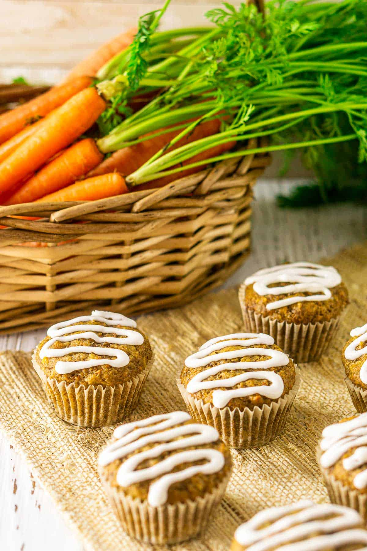 The carrot cake muffins in front of a basket with fresh carrots in it.