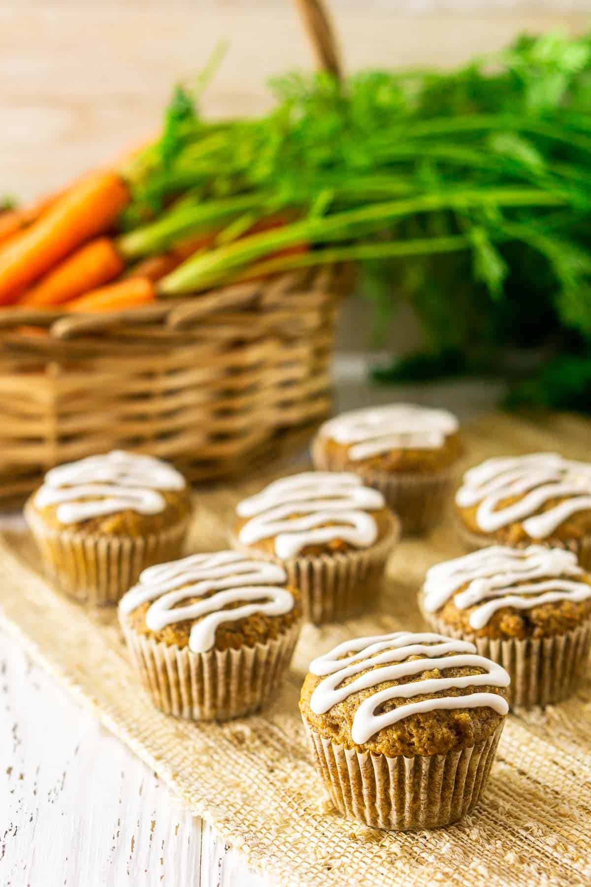 The carrot cake muffins on a white wooden board with a basket of carrots in the background.