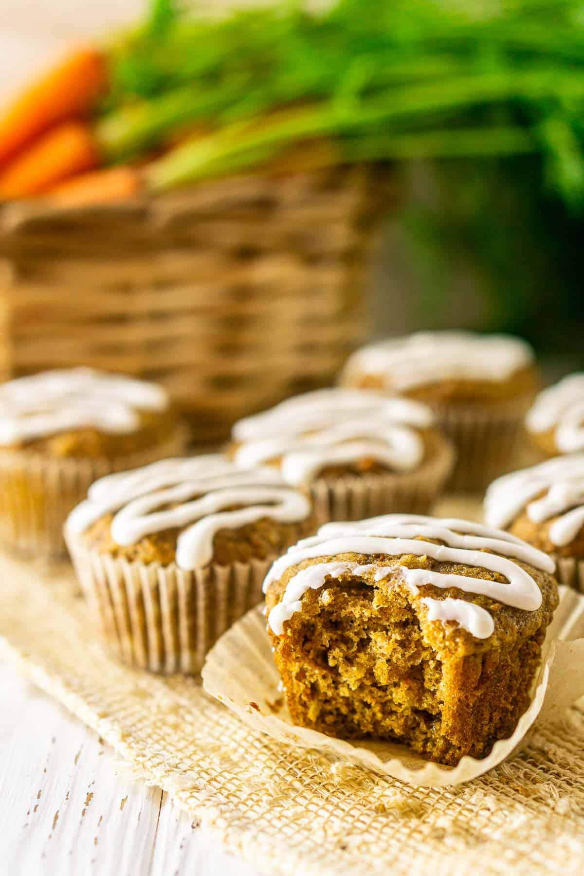 The carrot cake muffin after a bite has been taken out to show the fluffy interior.