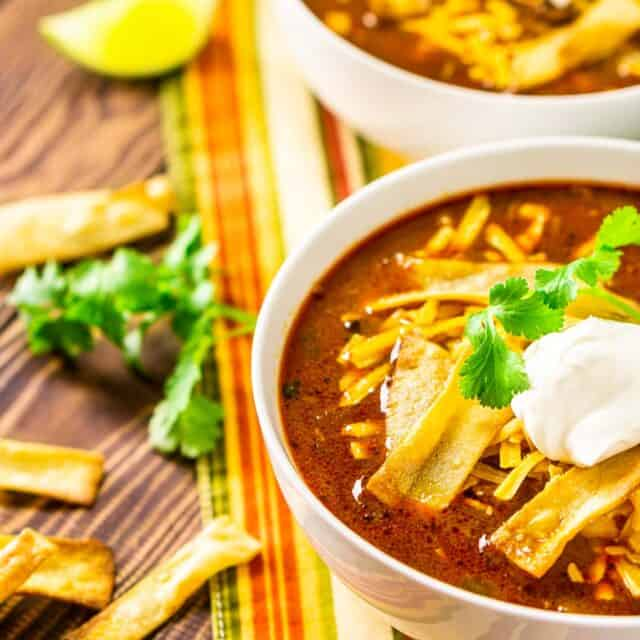 Two bowls of Instant Pot chicken enchilada soup on a colorful napkin with cilantro, tortilla chip strips and lime slices to the side.