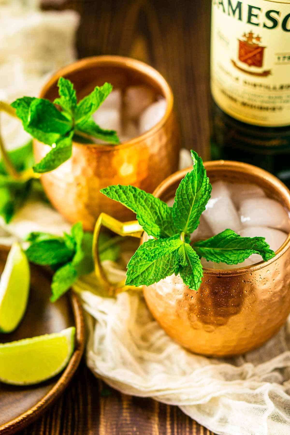 An aerial view of two whiskey mules on clothe with Jameson beside it.