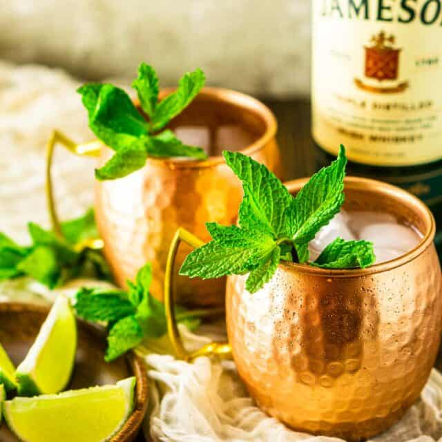 Two Irish mule cocktails on a cream-colored clothe with limes to the side and a bottle of Jameson behind them.