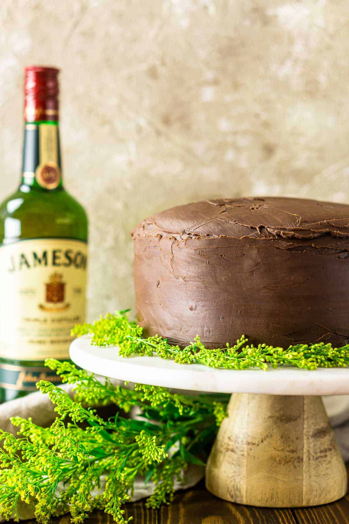 The Irish whiskey cake on a marble dessert stand with greenery on the side and a bottle of Jameson.