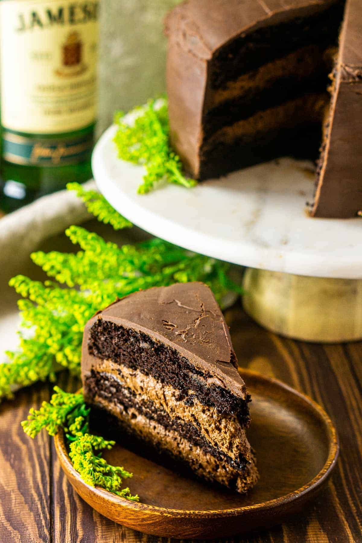 Looking down at a slice of Irish whiskey chocolate cake on a wooden plate with the greenery.