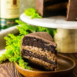 A slice of Irish whiskey chocolate cake on a wooden plate with a bottle of Jameson behind it.