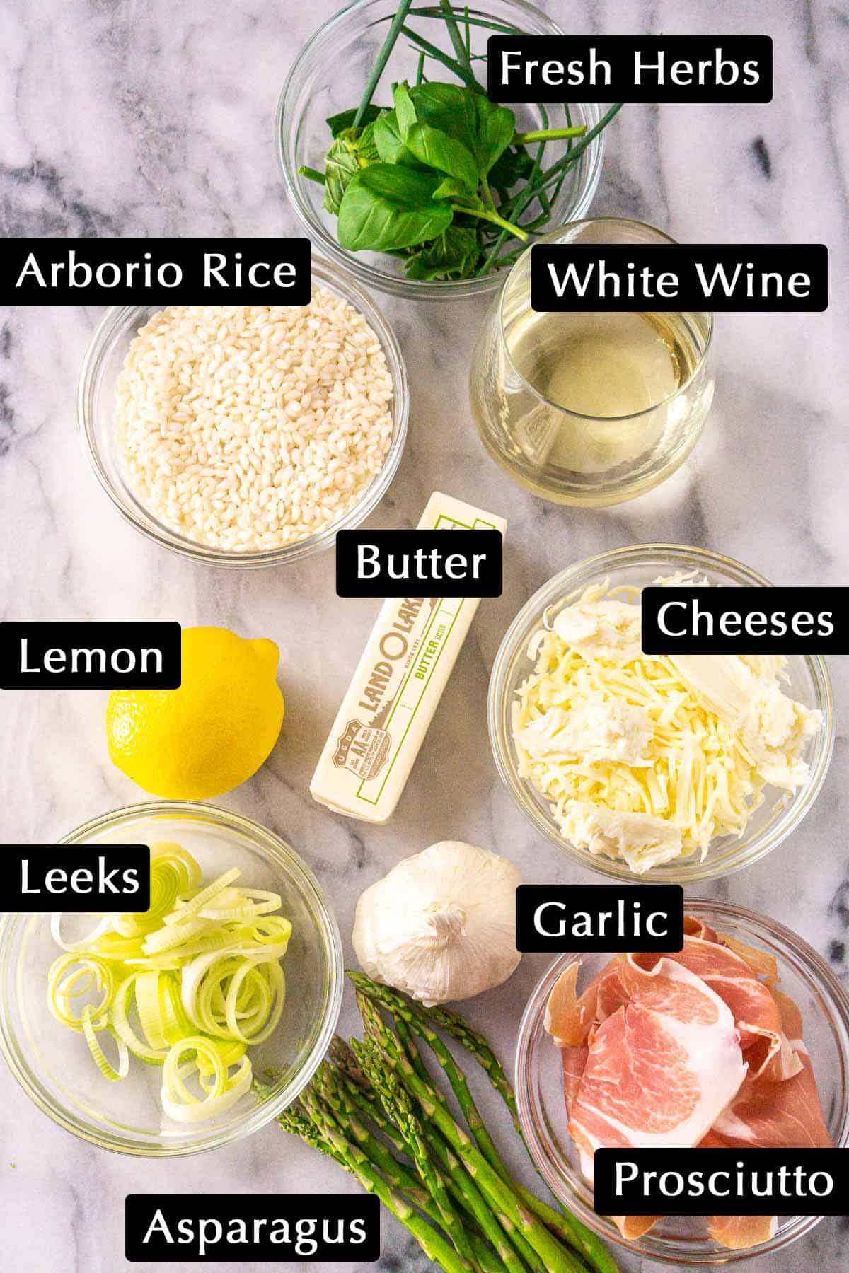 The spring risotto ingredients with labels on a white marble slab.
