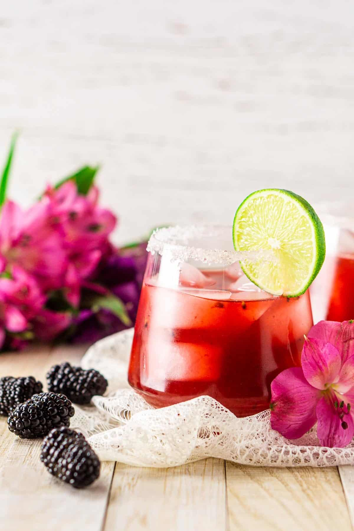 A blackberry margarita with a pink flower and blackberries to the side.
