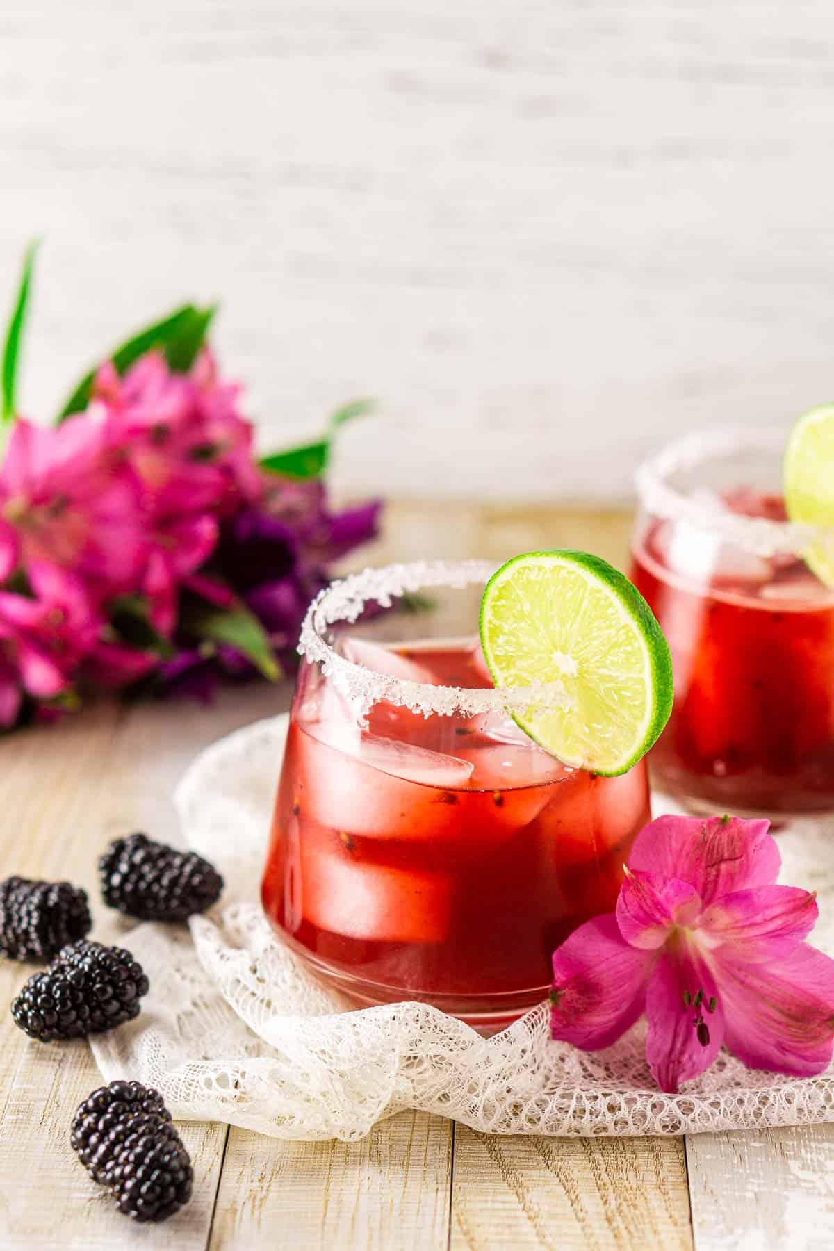 Two fresh blackberry margaritas on lace with pink and purple flowers in the background.