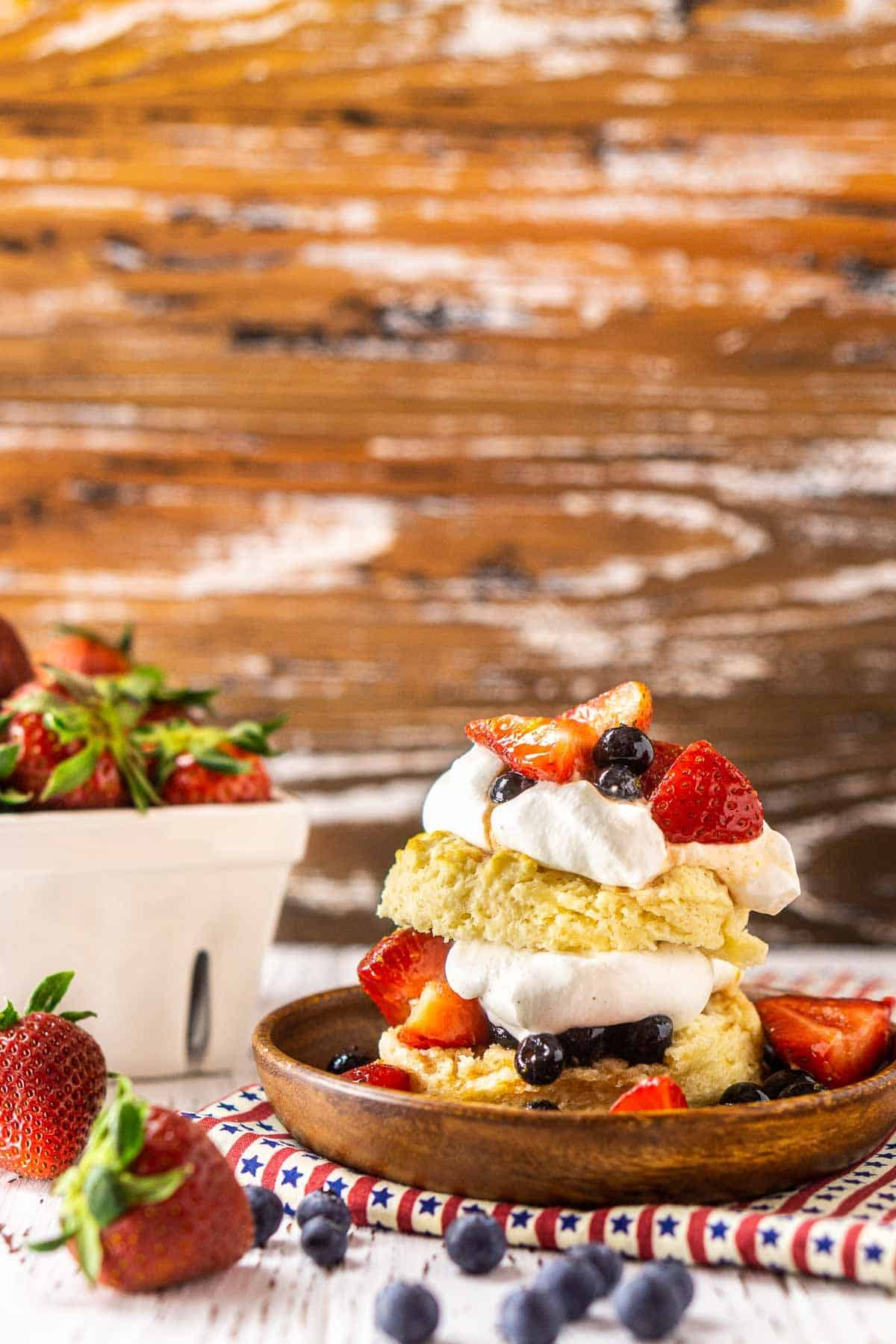 A blueberry-strawberry shortcake on a wooden plate and patriotic clothe with berries surrounding it.