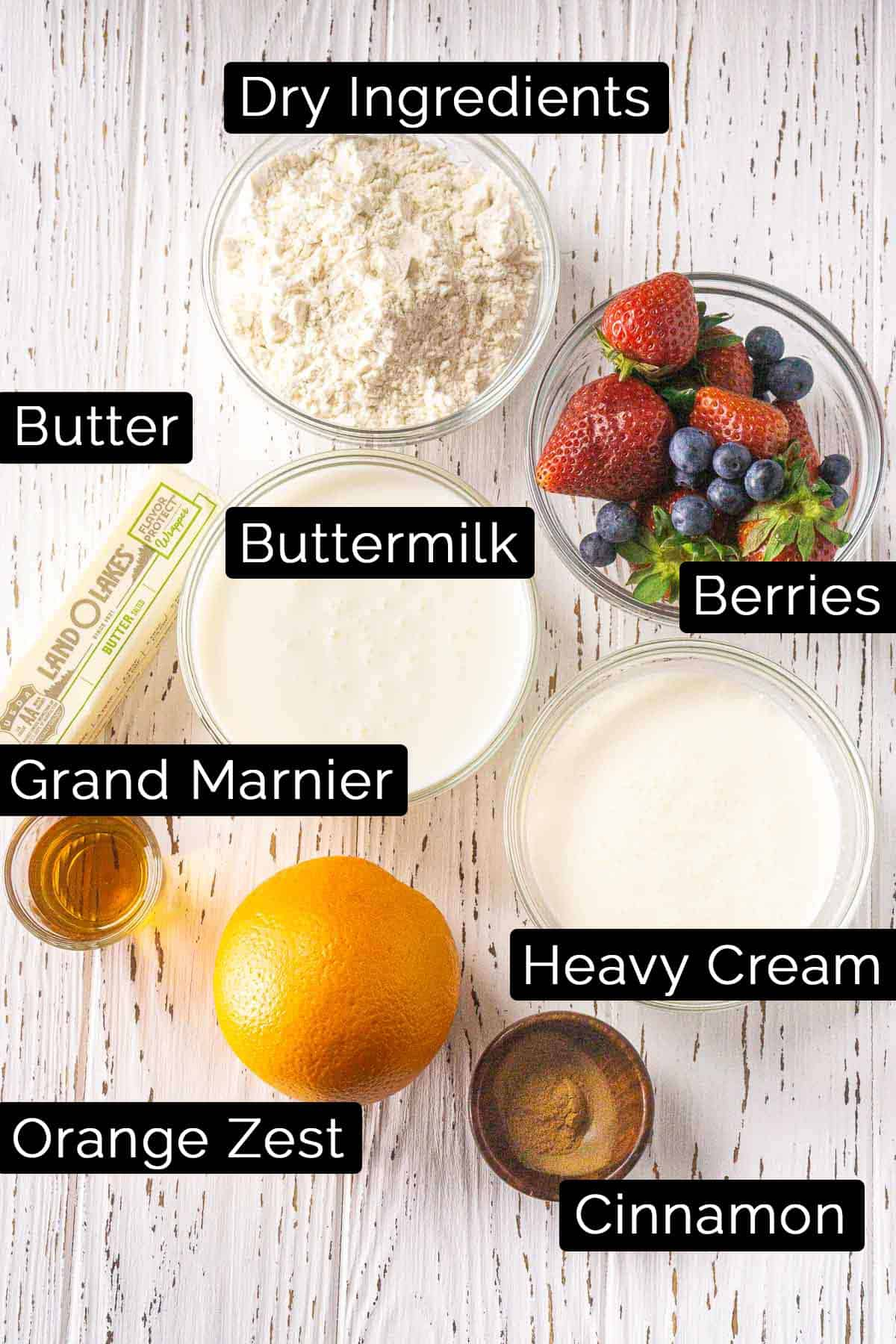 The blueberry strawberry shortcake ingredients on a white wooden board with labels.