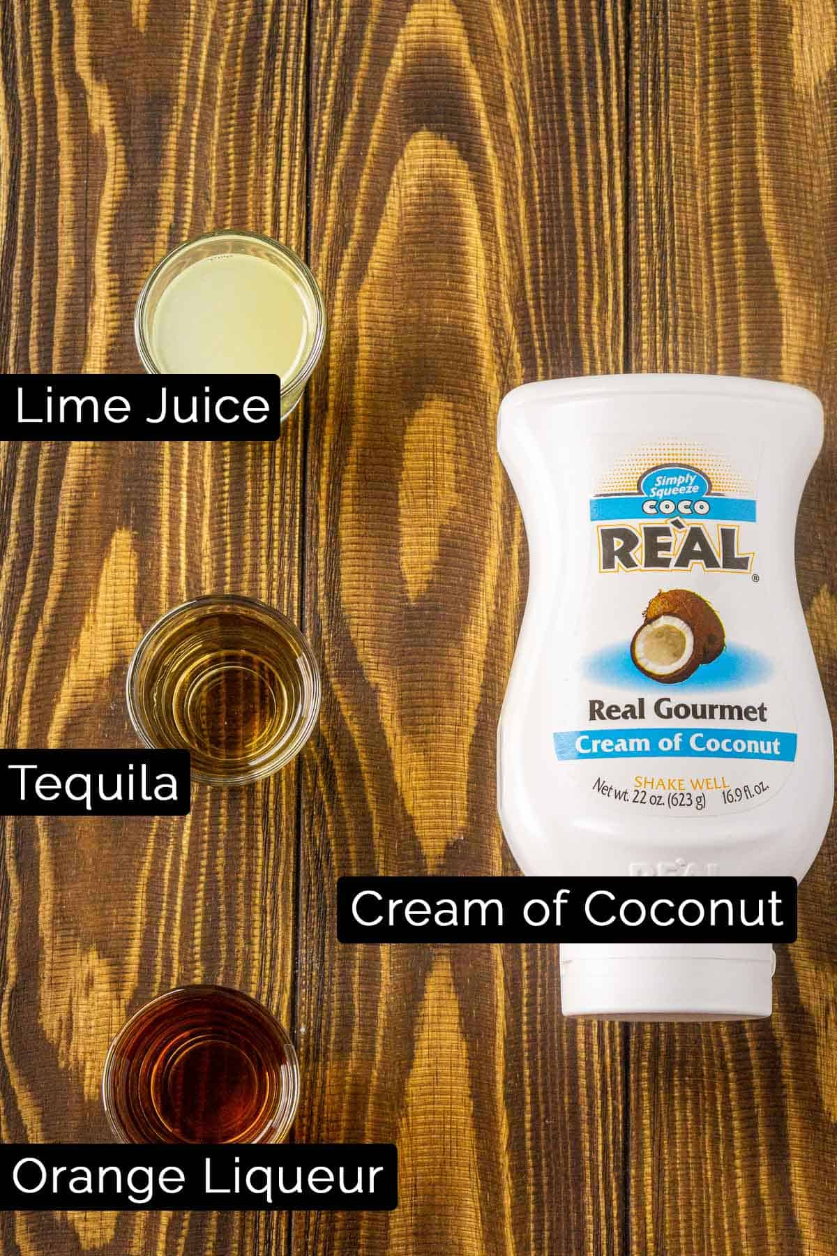 The coconut margarita ingredients with black and white labels on a wooden board.