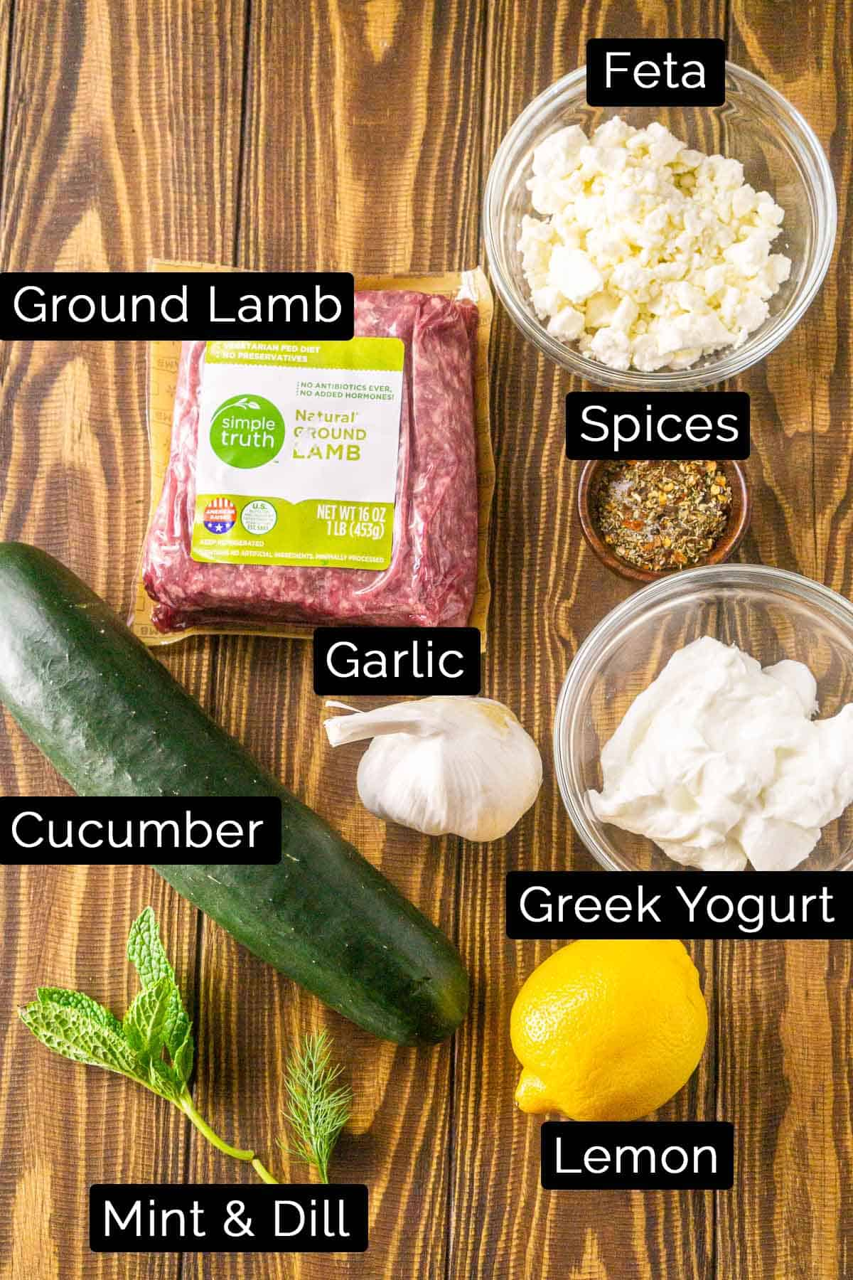 The minted lamb burger ingredients with black and white labels on a wooden board.