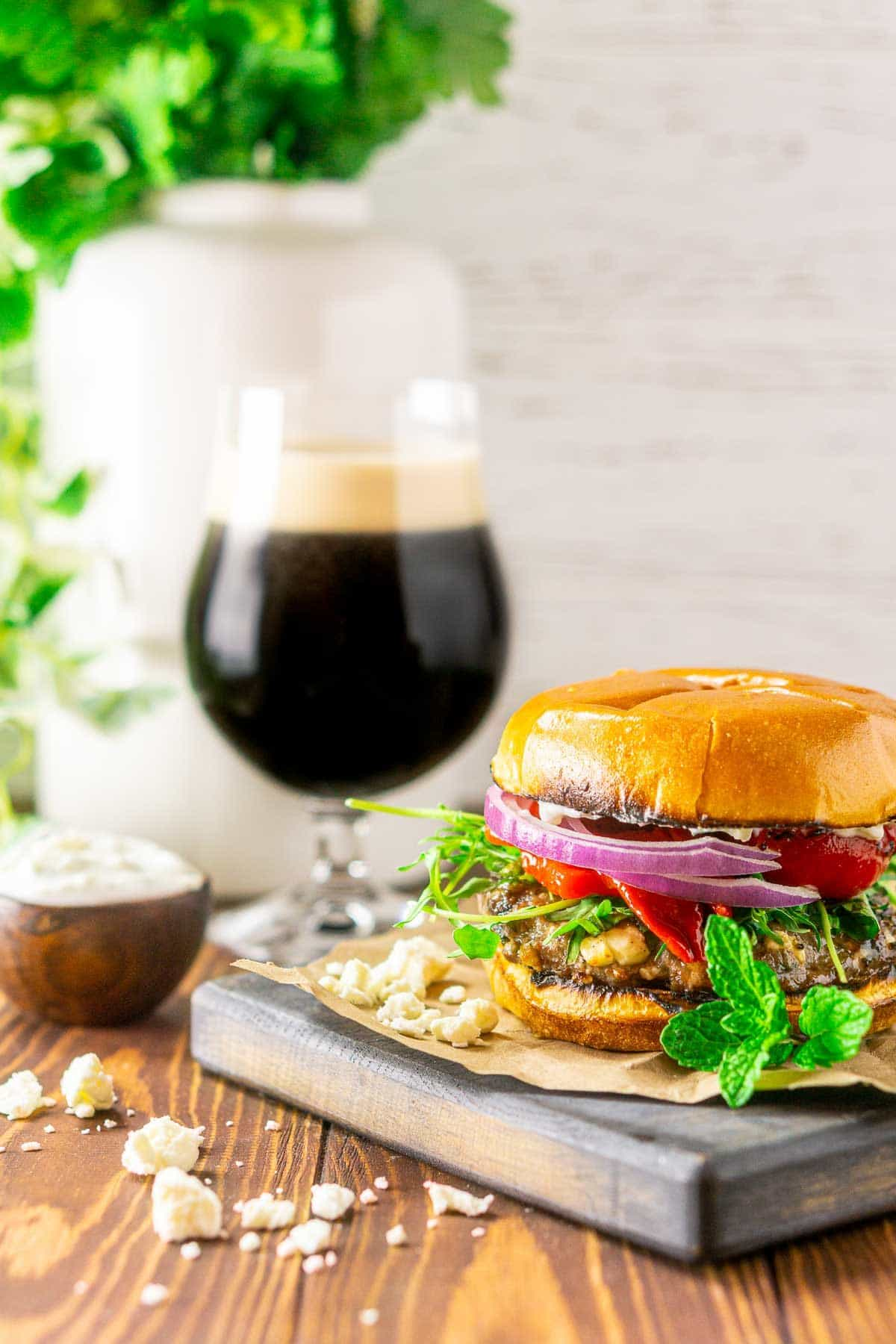 A minted lamb burger with a beer and greenery in the background.