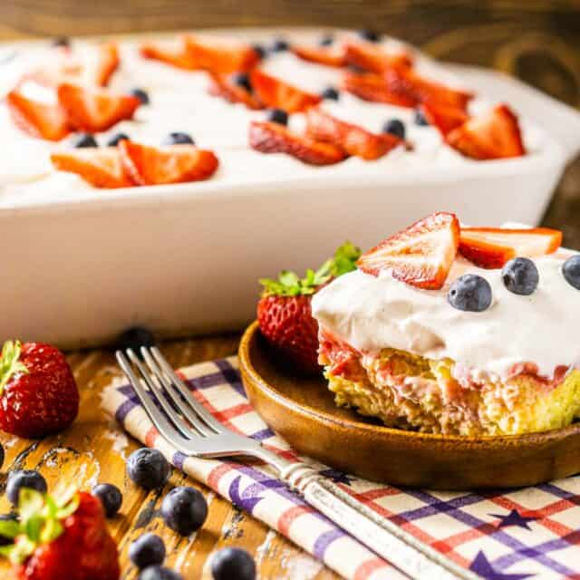 A slice of the 4th of July poke cake on a wooden plate with berries to the side.