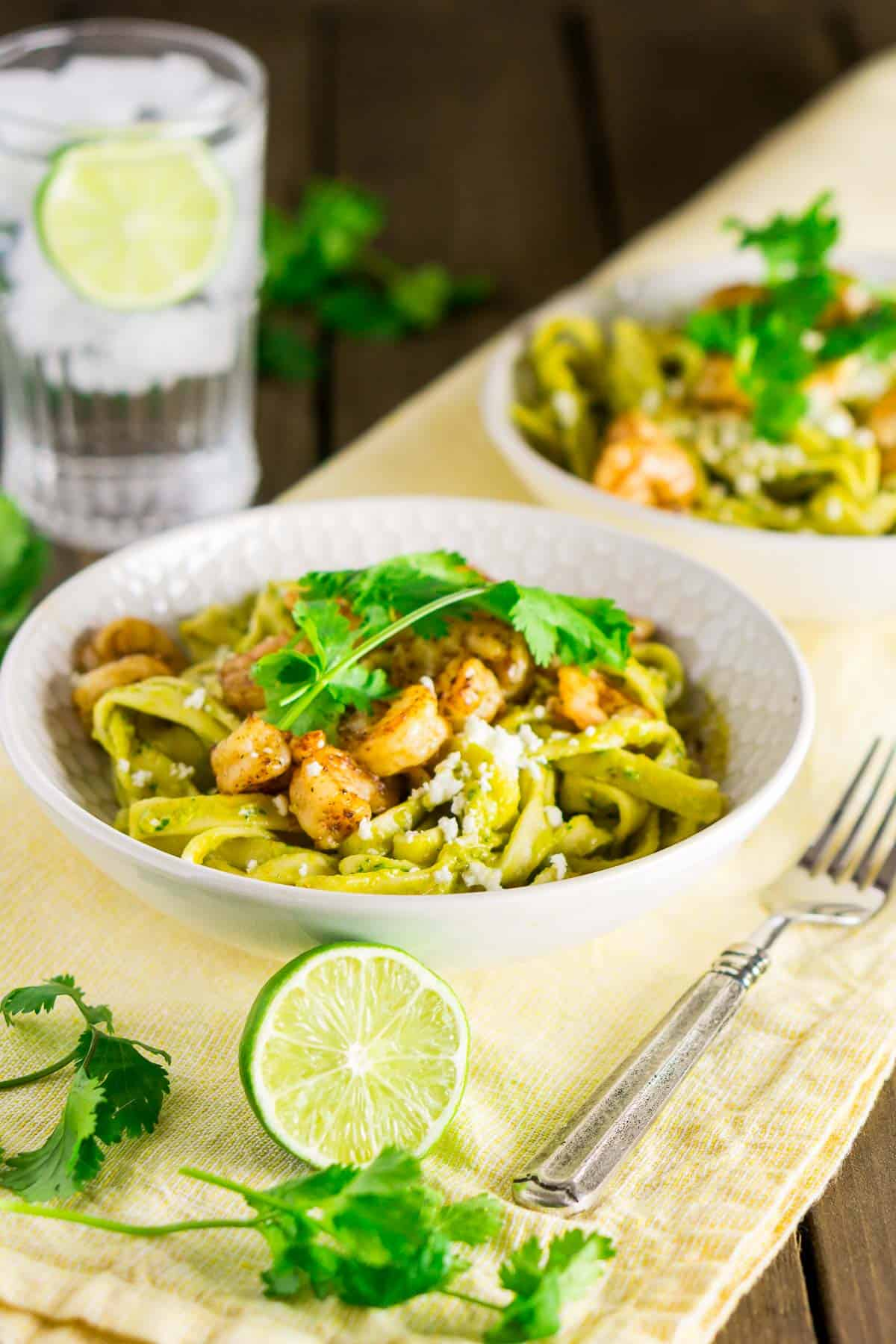 Two bowls of spicy avocado pasta with tequila shrimp on a yellow napkin with cilantro to the side.