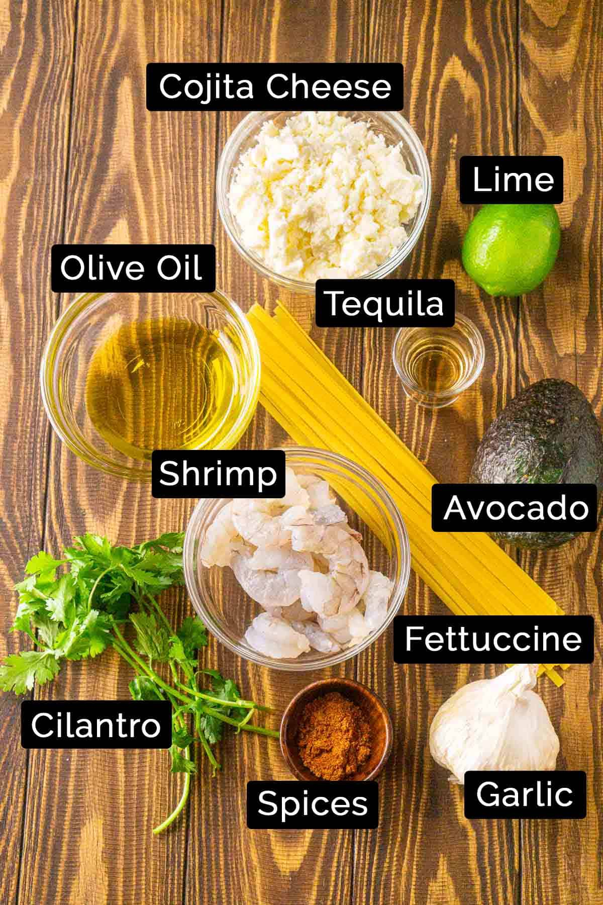 The spicy avocado pasta ingredients with black and white labels on a wooden board.
