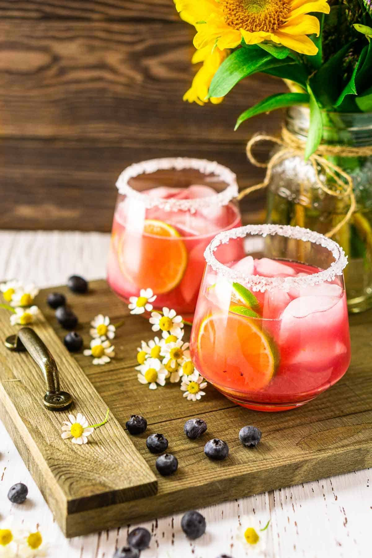 Looking down on two blueberry margaritas with flowers and blueberries around it.