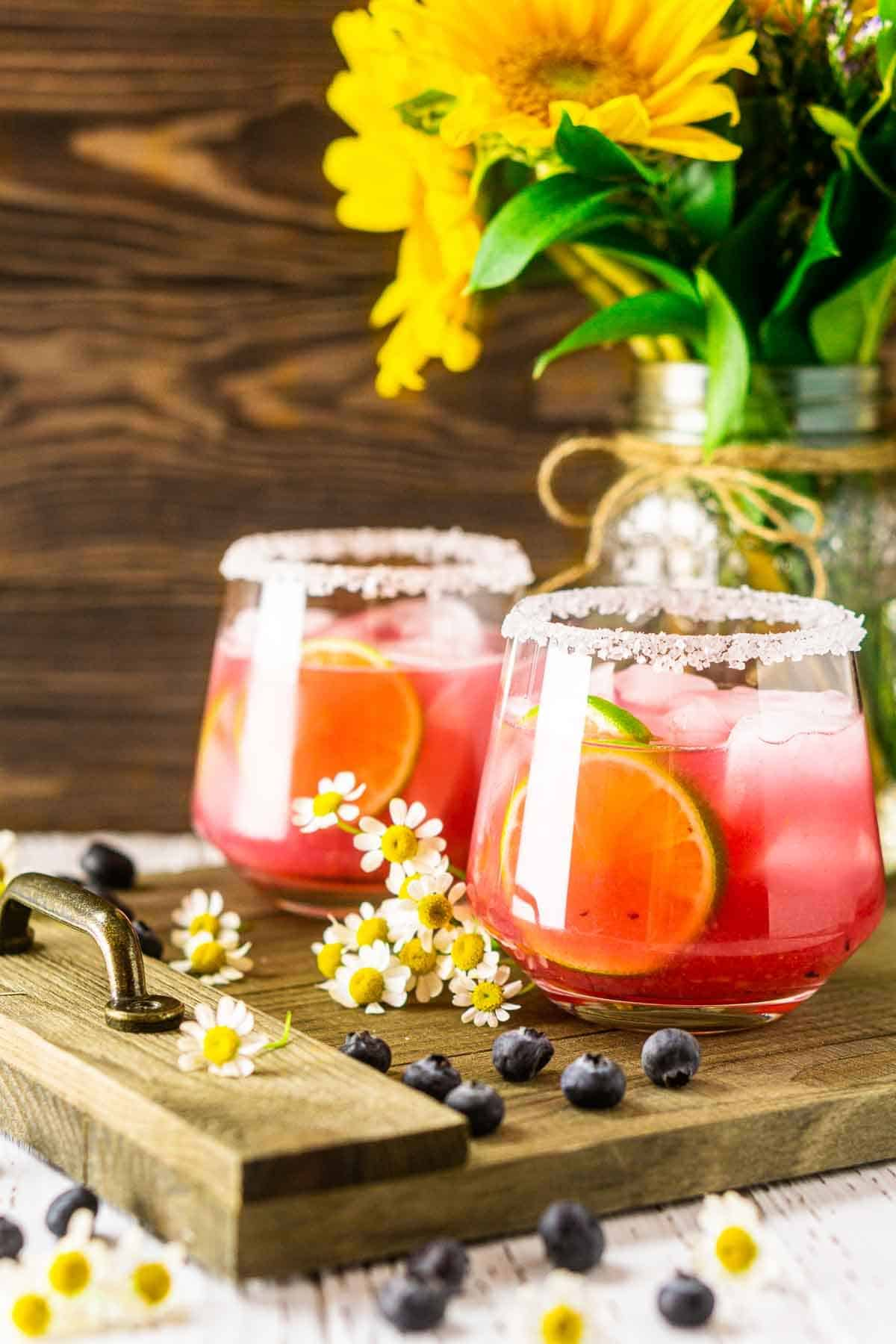 A close-up of a blueberry margarita on a wooden tray with flowers behind it.