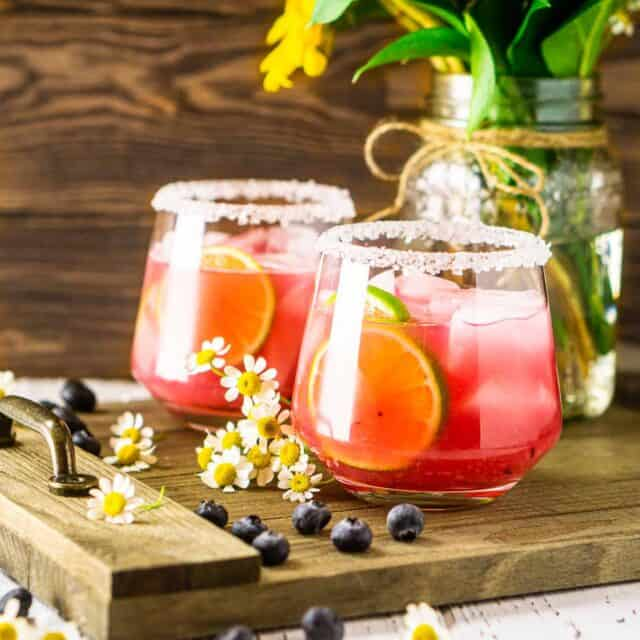 Two fresh blueberry margaritas with flowers and blueberries to the side on a wooden tray.