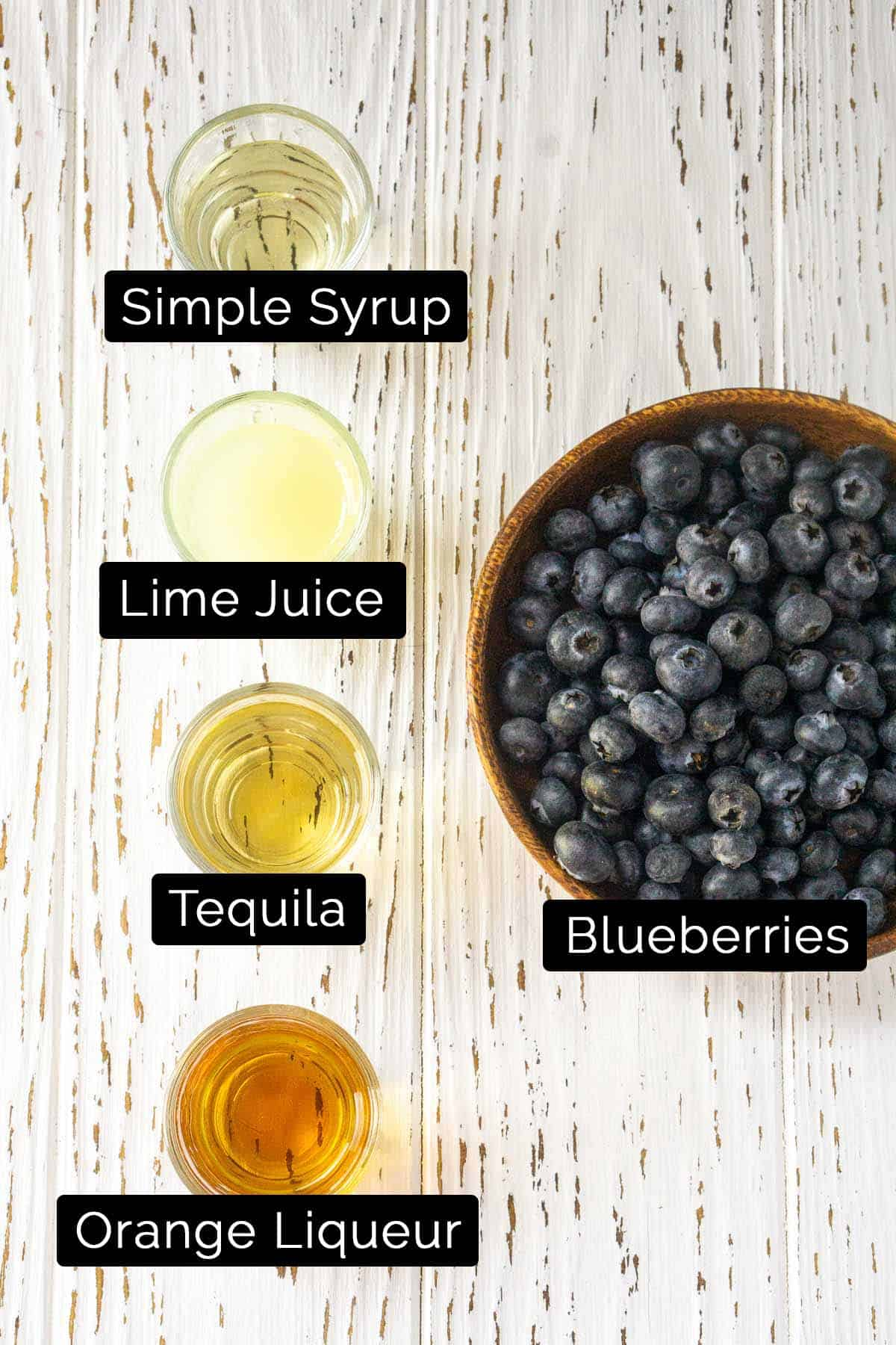 The blueberry margarita ingredients with white and black labels on a white board.