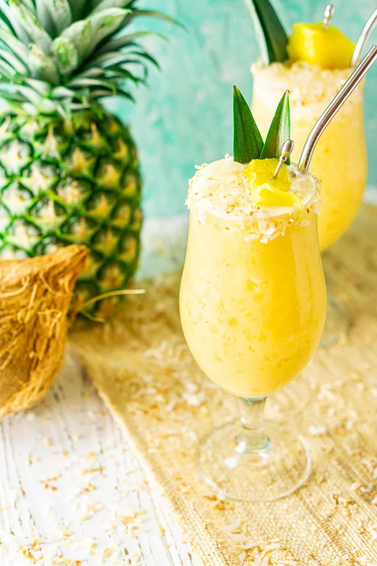 Two painkiller cocktails on a straw placemat with a pineapple and coconut to the side.
