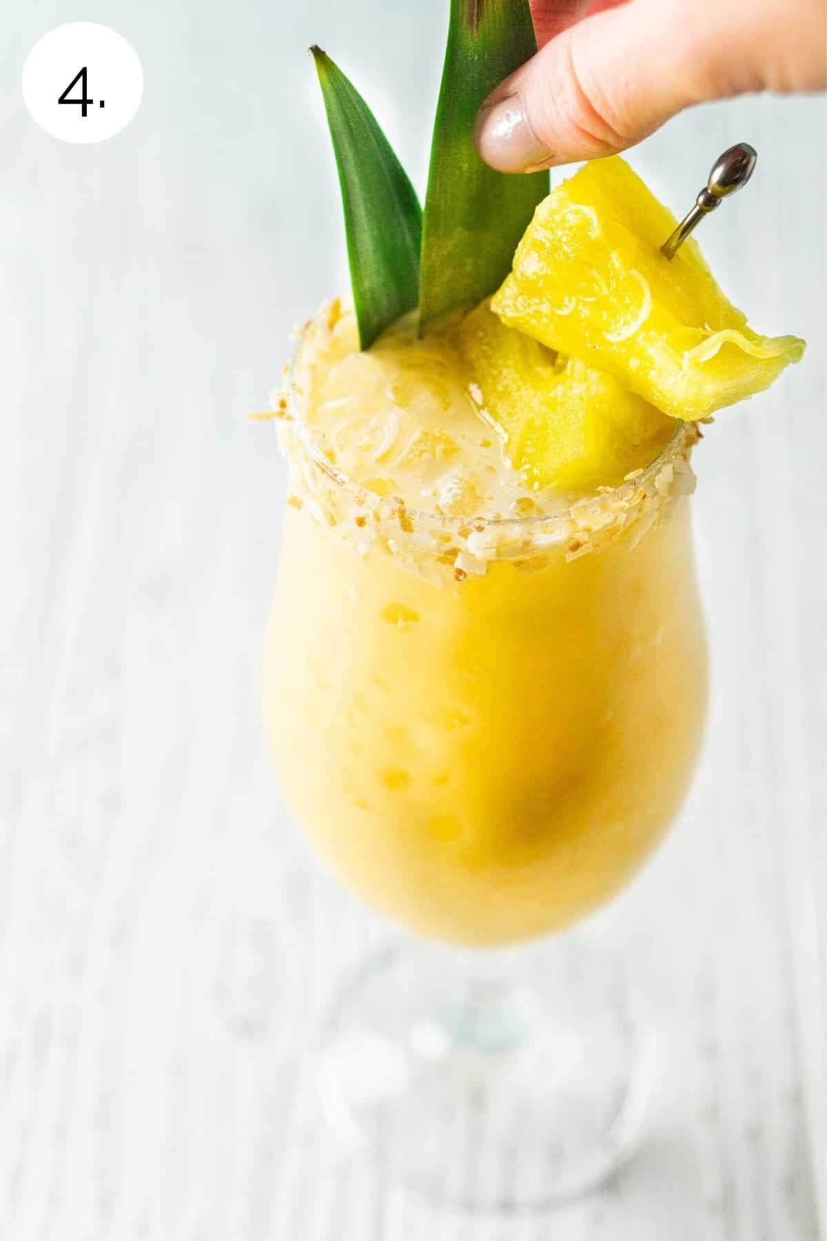 Garnishing the drink with pineapple leaves and pineapple chunks.