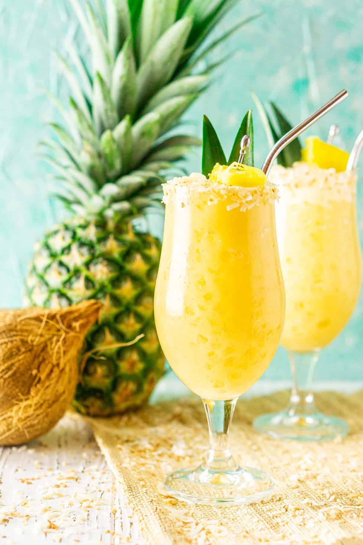 The painkiller cocktails with a pineapple and coconut behind them.