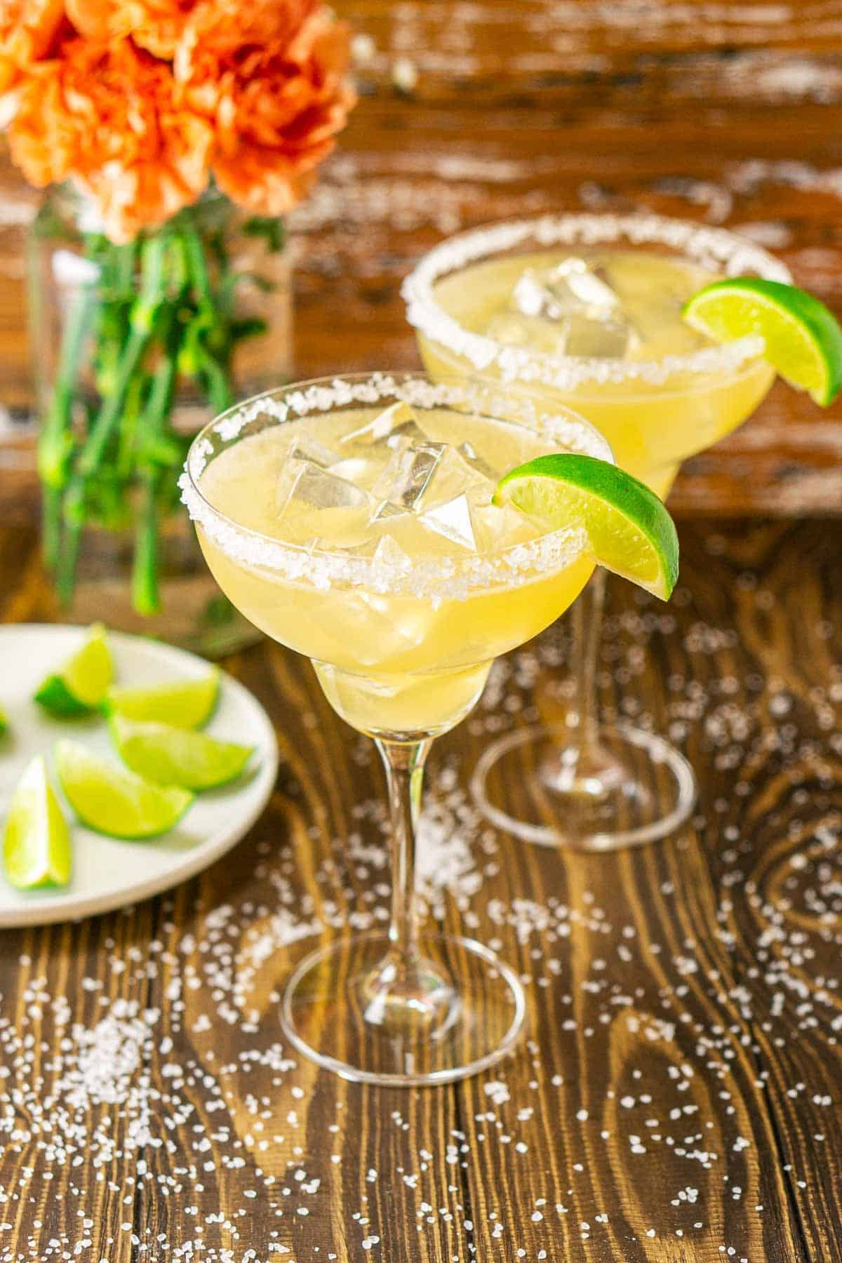 Looking down at two Cadillac margaritas with a plate of limes to the left.