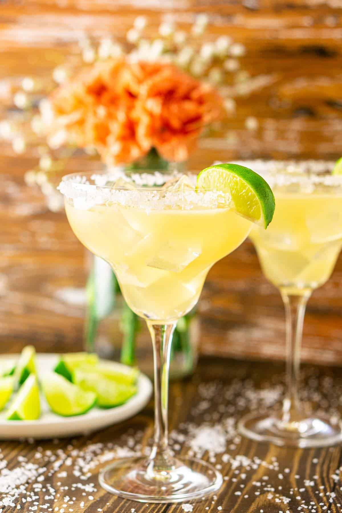 A close-up of a Cadillac margarita with orange flowers on the left.