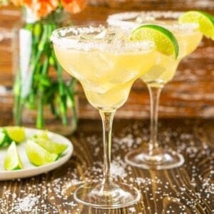 Two Cadillac margaritas with salt around them and limes and flowers to the side.